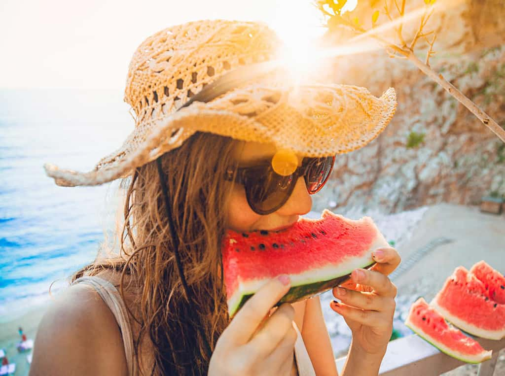 young woman having fun and eating juicy fresh watermelon outdoor at sunset time with sunflare in summer time